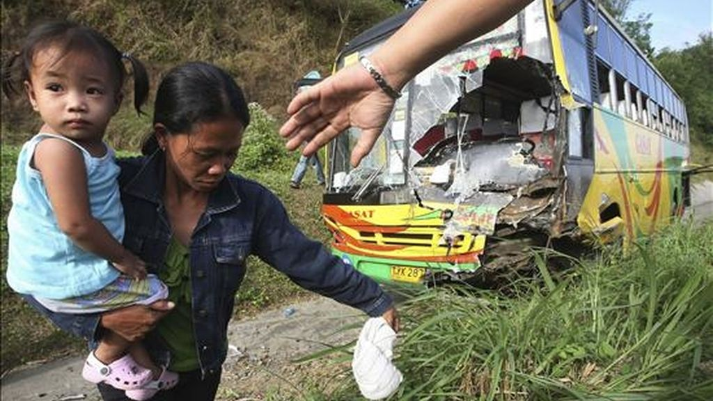 Una mujer camina con su hija en brazos tras sobrevivir a un accidente entre un autobús y un todoterreno en la provincia de Batangas al sur de Manila (Filipinas). EFE