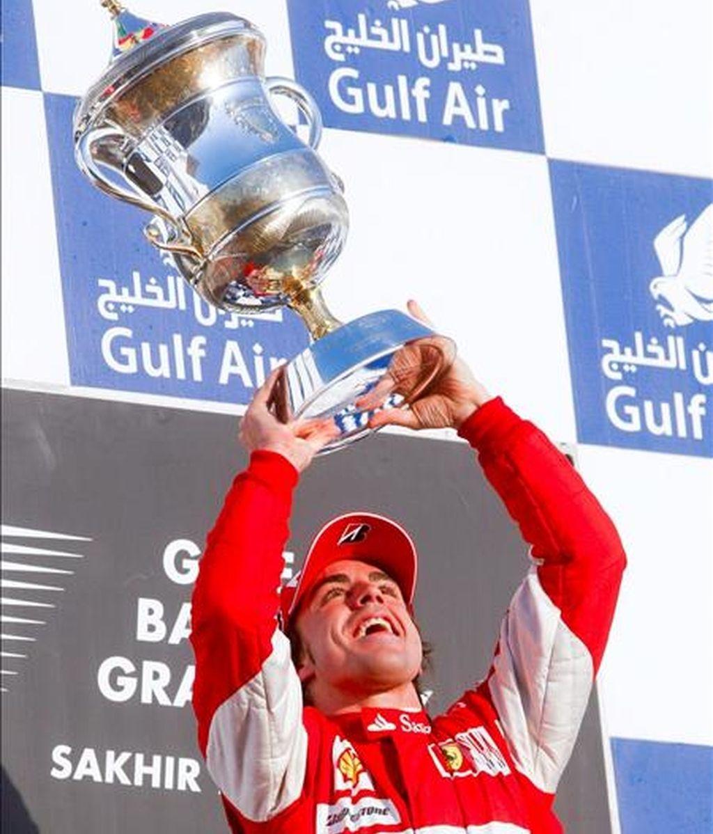 El piloto español de la escudería Ferrari, Fernando Alonso, levanta su trofeo de ganador en el podio del Gran Premio de Bahrein hoy en el Circuito Internacional de Bahrein en Sakhir. EFE