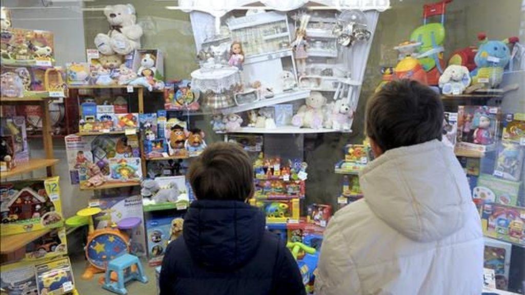 Dos niños miran el escaparate de una juguetería