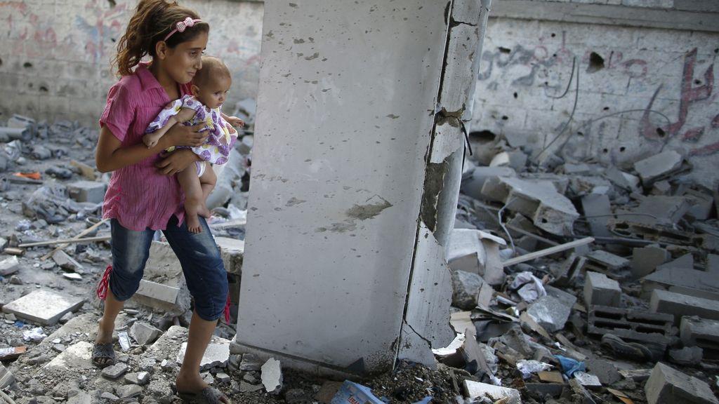 Un niña camino con su hermana por los restos de una mezquita en Gaza