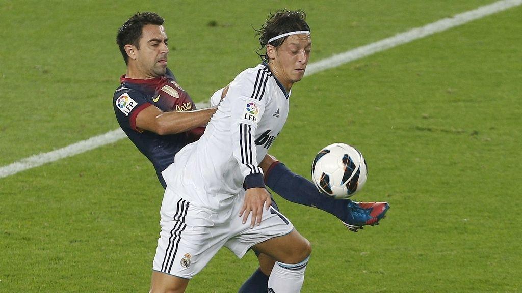 Özil y Xavi pelean por un balón