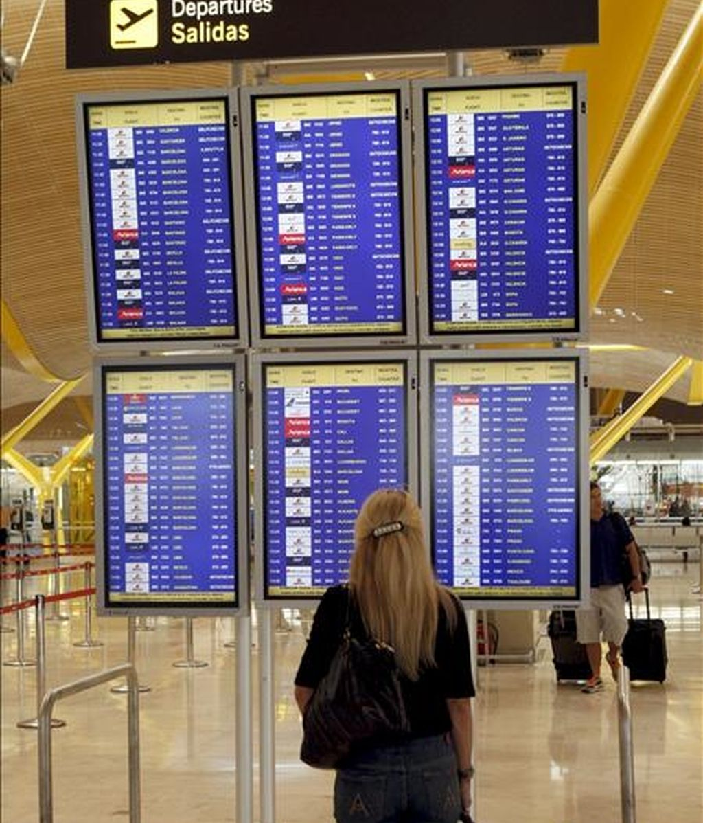 Una joven comprueba la salida de su vuelo en la T-4 de Barajas durante la jornada de paro de los tripulantes de cabina de Iberia en protesta por la falta de acuerdo con la empresa en la negociación del nuevo convenio colectivo. EFE