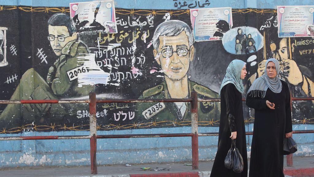 Mujeres palestinas pasean por un muro en el que aperecen pintados soldados israelíes en el norte de Gaza