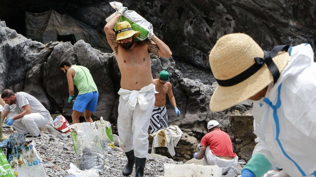 Voluntarios limpian el fuel que ha llegado a la costa