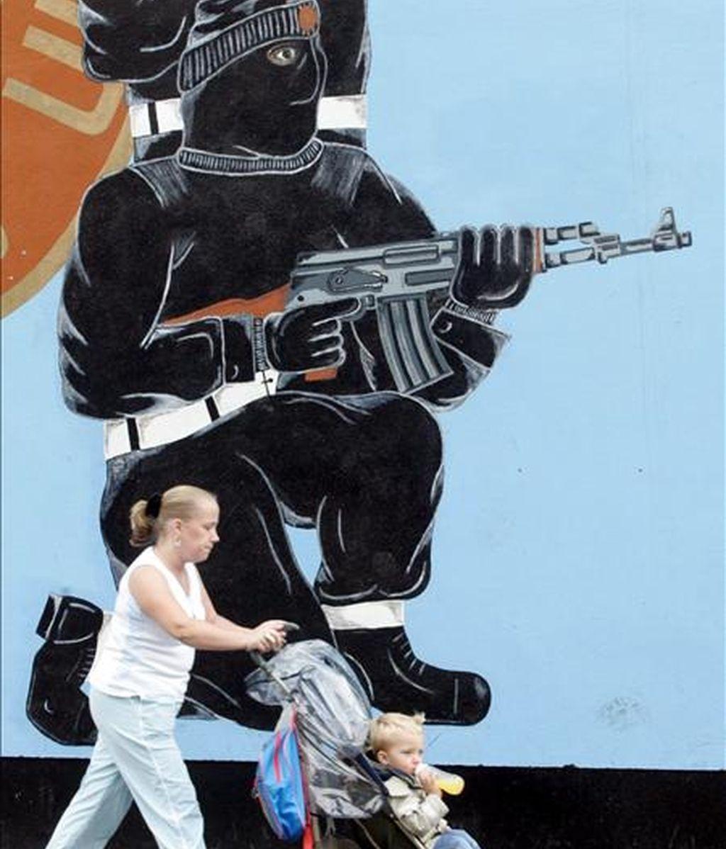 Una mujer pasea con su hijo por delante de un mural de la Fuerza de Voluntarios del Ulster (UVF) en la calle Shankill, oeste de Belfast. EFE/Archivo