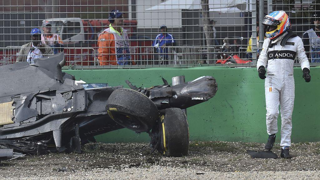Fernando Alonso mira asombrado cómo ha quedado su monoplaza tras el accidente (20/03/2016)