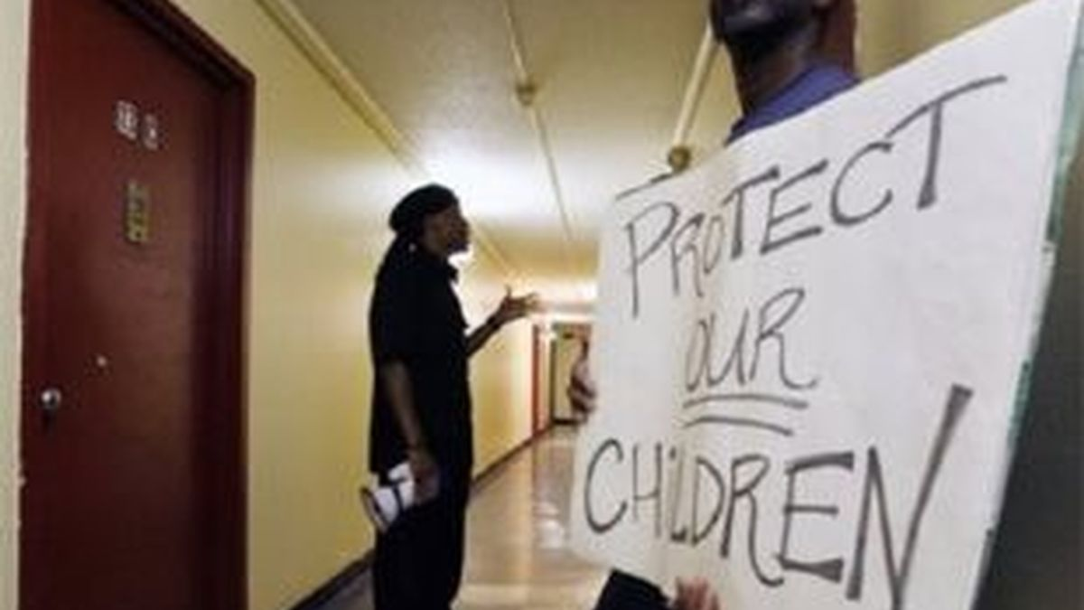 Un hombre exhibe un cartel de protesta ante la puerta del apartamento donde se produjo la violación de una menor, en la ciudad de Trenton. Foto: AP