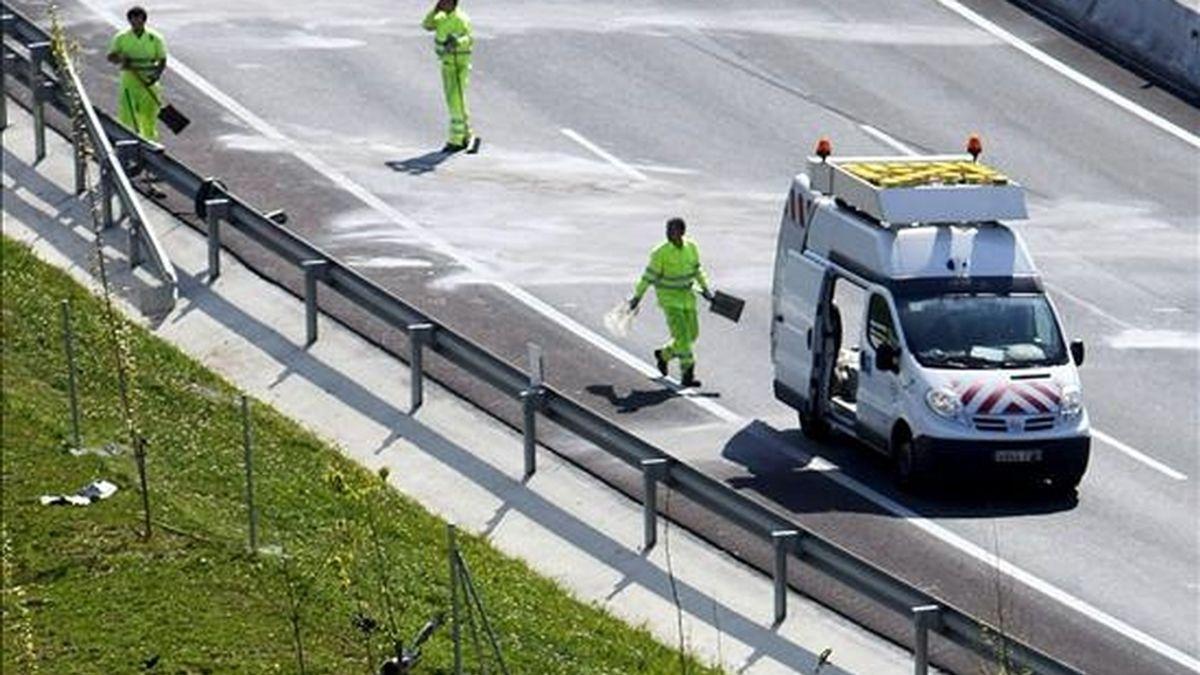 En la imagen, varios operarios tratan de limpiar el asfalto y algunos restos de un vehículo tras un accidente. EFE/Archivo