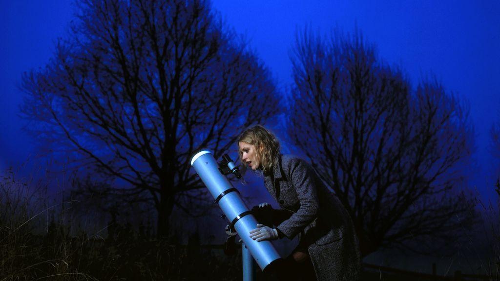 Mujer mira por un telescopio