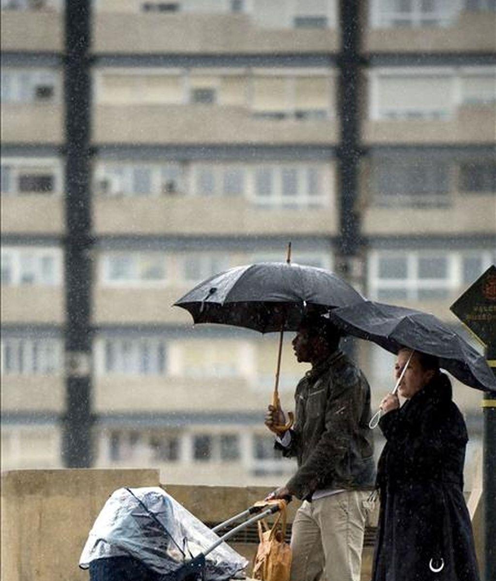 Una familia se protege con un paraguas de la lluvia. EFE/Archivo