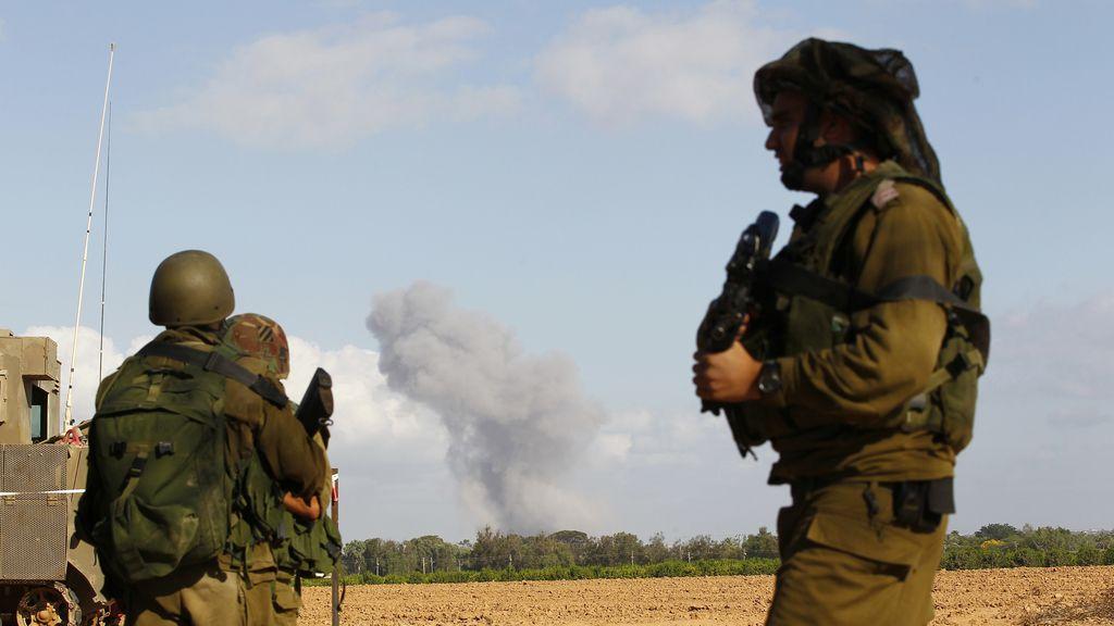 Soldados israelíes observan una columna de humo en Gaza