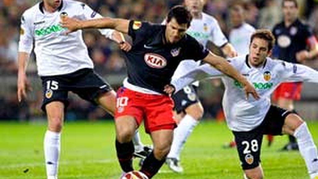 """Sergio """"Kun"""" Agüero pelea un balón con los jugadores del Valencia Ángel Dealbert y Jordi Alba. Foto: EFE."""