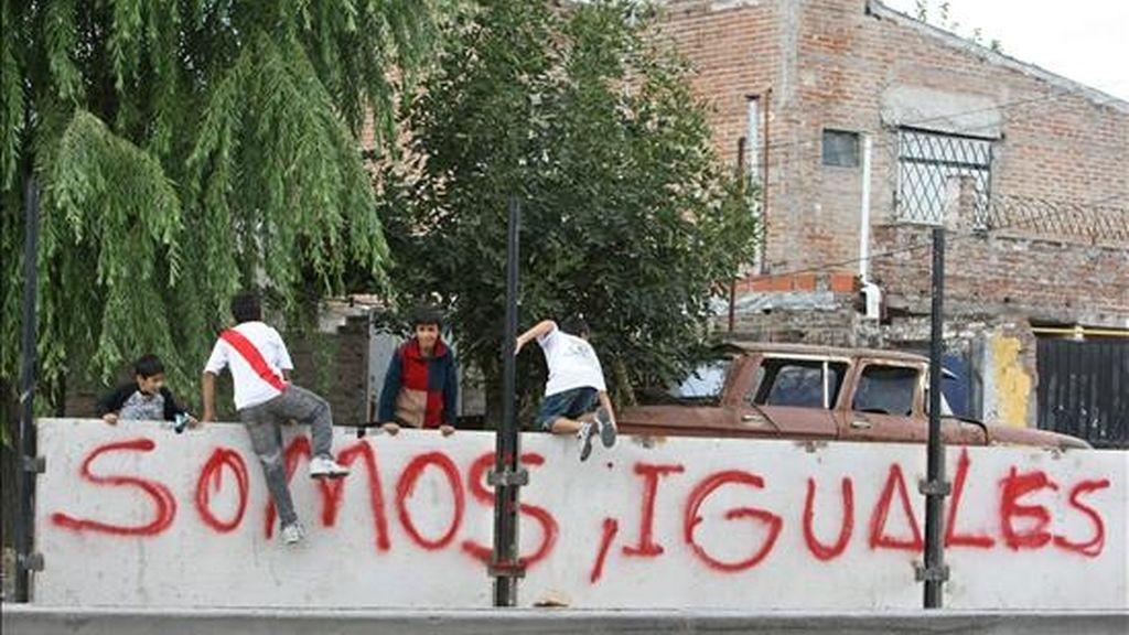 Niños de un barrio de la periferia de la ciudad de Buenos Aires (Argentina), saltan por encima de un muro que se construye para separar una lujosa zona residencial de la localidad de San Isidro con su vecina de San Fernando. EFE