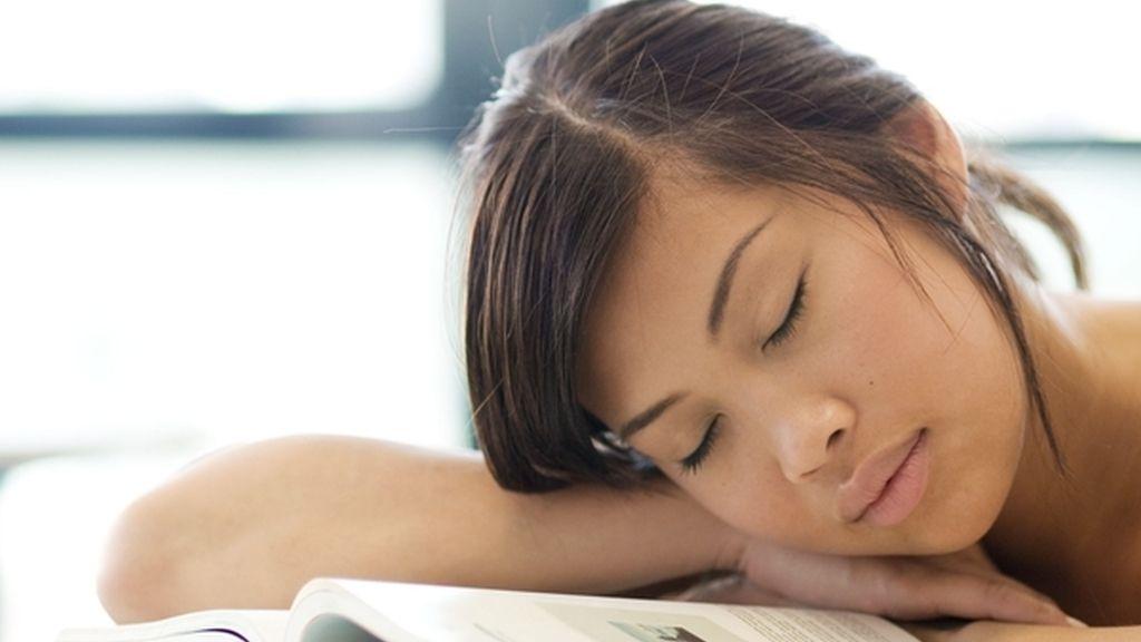 Chica durmiendo sobre libros