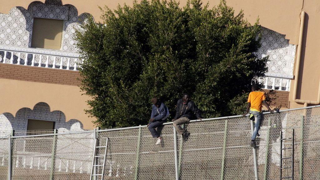 Inmigrantes encaramados a la valla fronteriza en Melilla