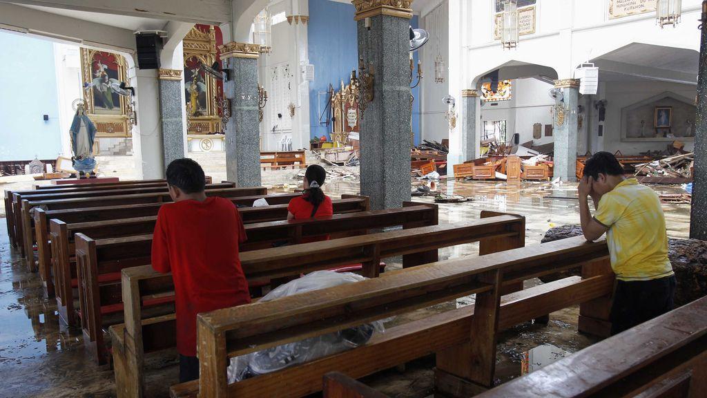 Tailandeses rezando en una Iglesia destrozada tras el paso del tifón