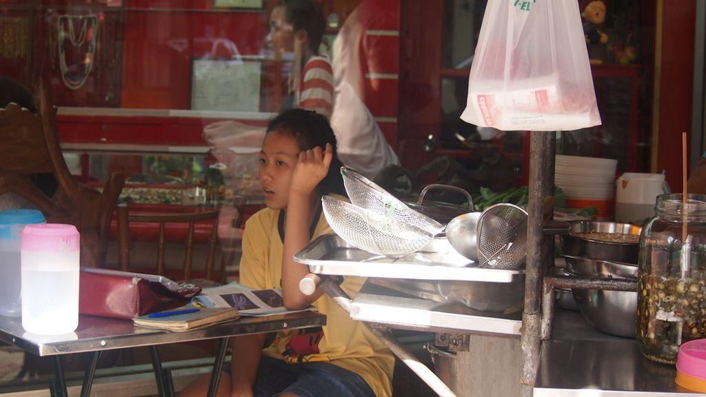 Adolescente estudiando en el puesto de comida de su madre