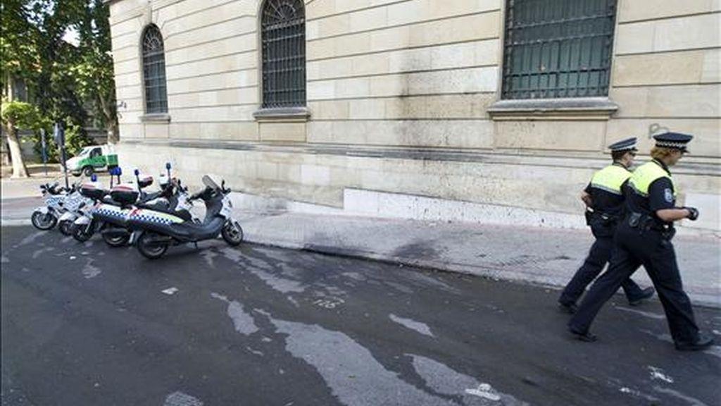 Dos policías municipales pasan junto a un coche atacado con un cóctel molotov en Vizcaya. EFE/Archivo