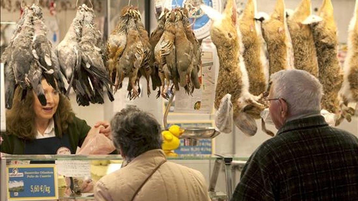 Dos personas compran en una pollería. EFE/Archivo