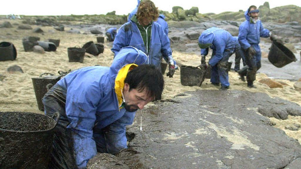 """Un grupo de voluntarios limpia de fuel procedente del vertido del """"Prestige"""" una cala de Carnota, a la hora de la comida de Navidad y bajo una fuerte lluvia en 2002 ."""