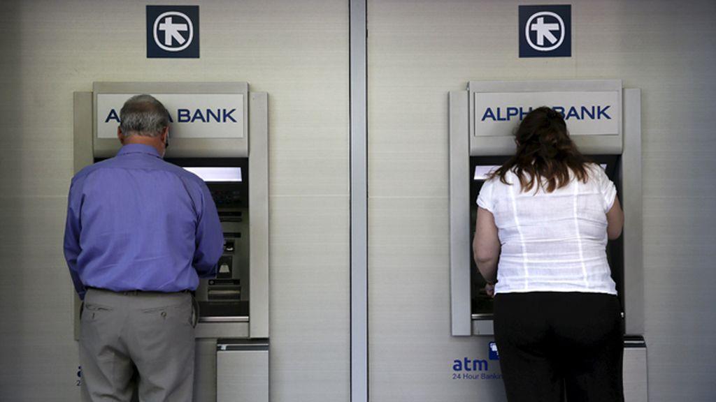 Varias personas sacan dinero de un banco en Grecia