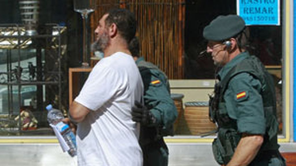 Agentes de la Guardia Civil conducen a uno de los detenidos al regitro de una de las dos carnicerías del barrio pamplonés de San Jorge FOTO: EFE