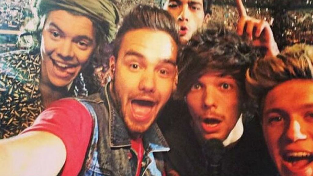 Los cinco One Direction casi no caben en un selfie.... sobre todo si además quieren sacar todos los estadios que llenaron en su gira de 2014