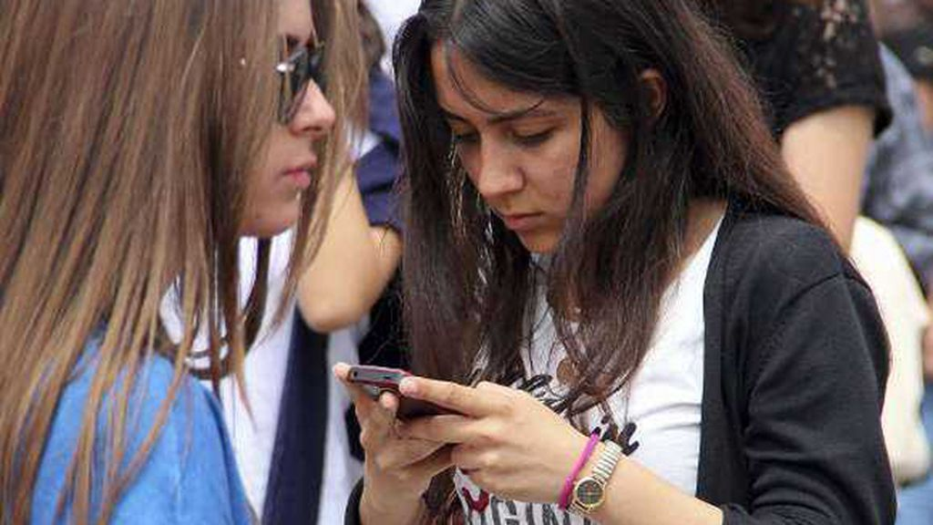 Una joven consulta su móvil