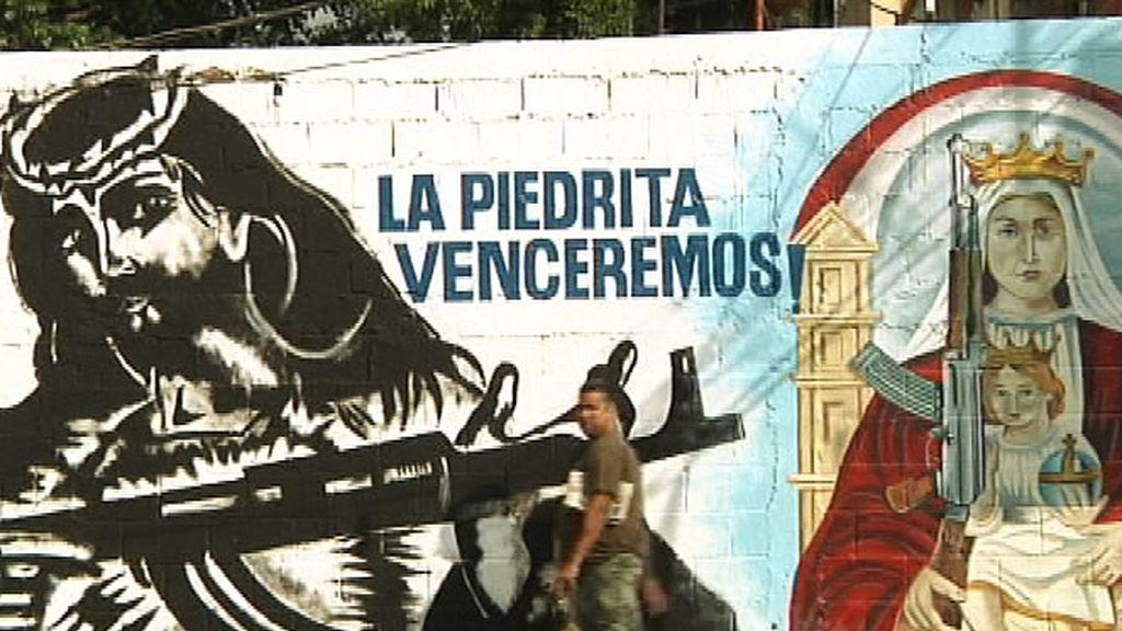 Una pintada en un muro con Jesucristo y la Virgen con un fusil en la mano