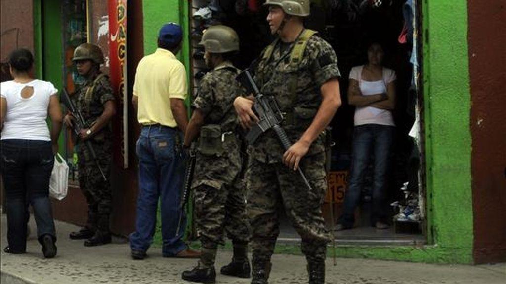 Militares hondureños custodian uno de los puntos estratégicos de Tegucigalpa (Honduras). El Gobierno inició este viernes la distribución del material para celebrar el domingo una consulta popular sobre una reforma a la Constitución, mientras miles de hondureños se manifiestan en contra de esta iniciativa. EFE