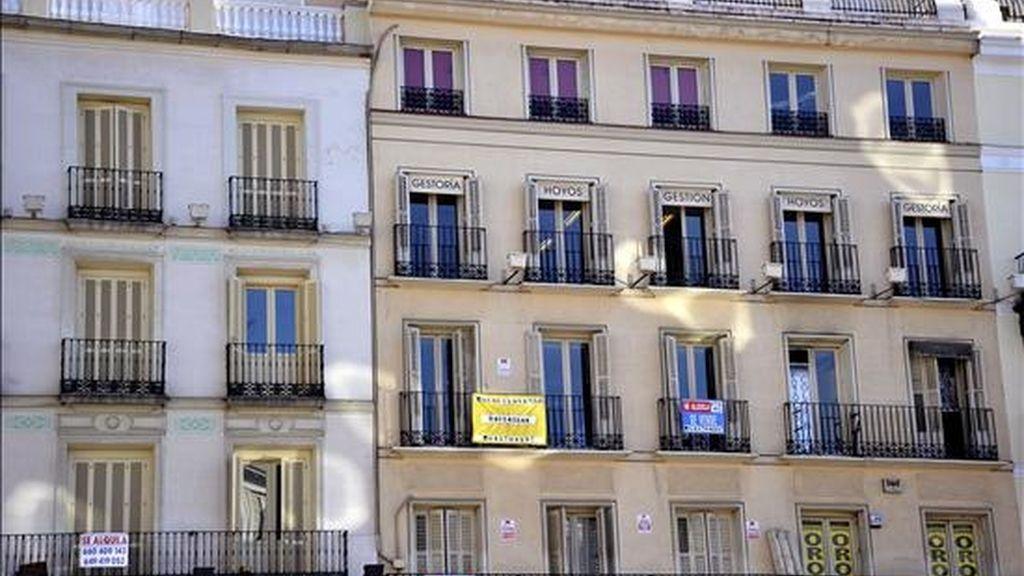 Fachada de un edificio con carteles de venta y alquiler de pisos.