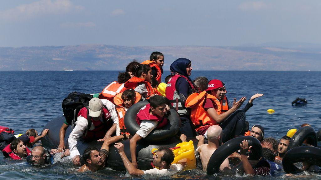 Refugiados sirios y afganos alrededor de un bote que desinfla antes de llegar a la isla griega de Lesbos