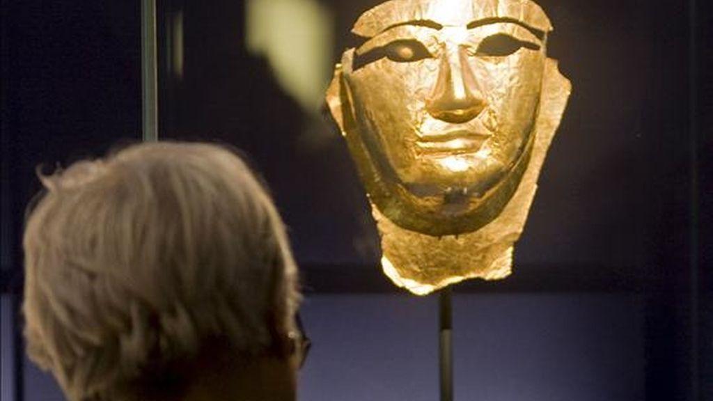 """En la imagen, una persona observa una máscara funeraria en la exposición sobre el antiguo Egipto """"Las puertas del cielo"""", en el museo del Louvre, en París, Francia. EFE/Archivo"""