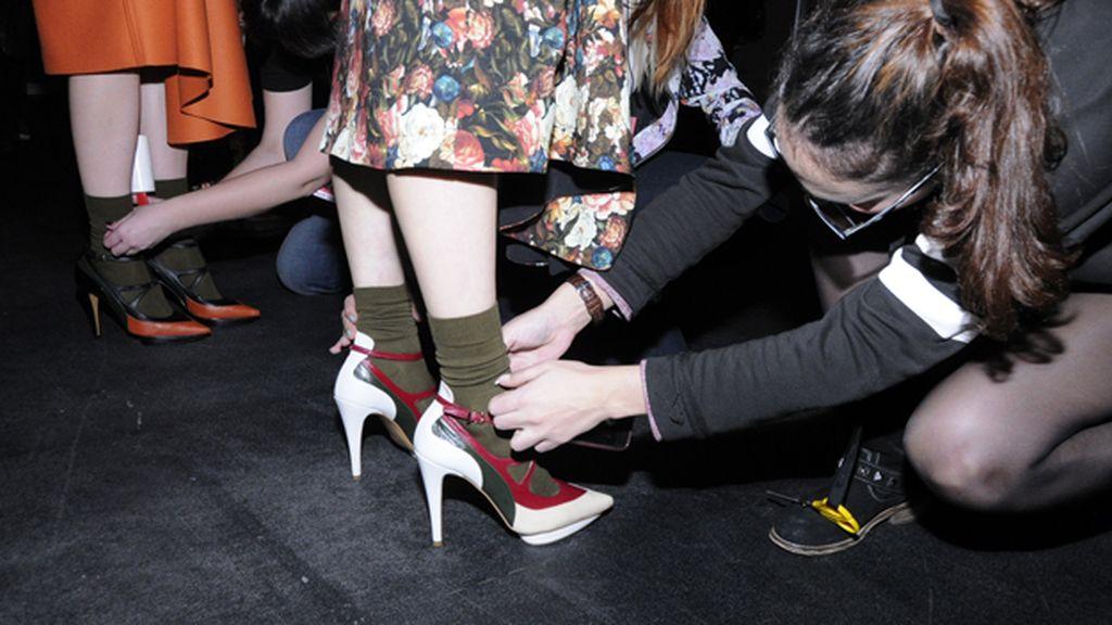 El equipo de Ana Locking colocando los zapatos de las modelos ya camino de la pasarela