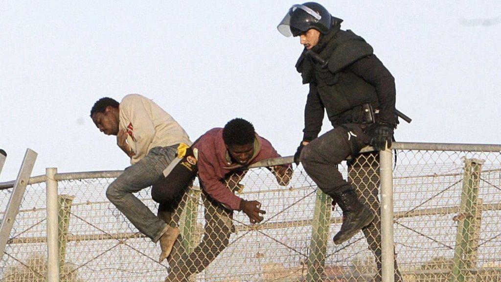 Inmigrantes encaramados a la valla de Melilla tras un nuevo salto