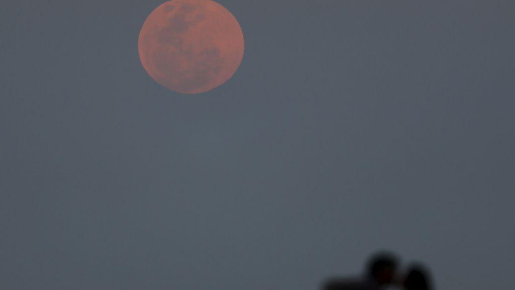 La sombra de una pareja frente a la luna en Río de la Plata, Buenos Aires, Argentina