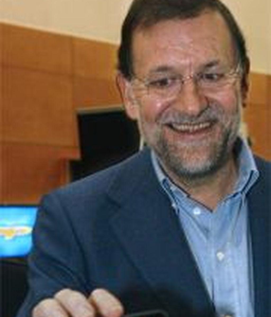 Rajoy sostiene un ipod con un video suyo en la conferencia del PP sobre tecnologías. EFE
