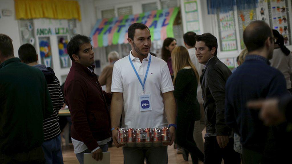 Un interventor del Partido Popular carga con latas de cerveza