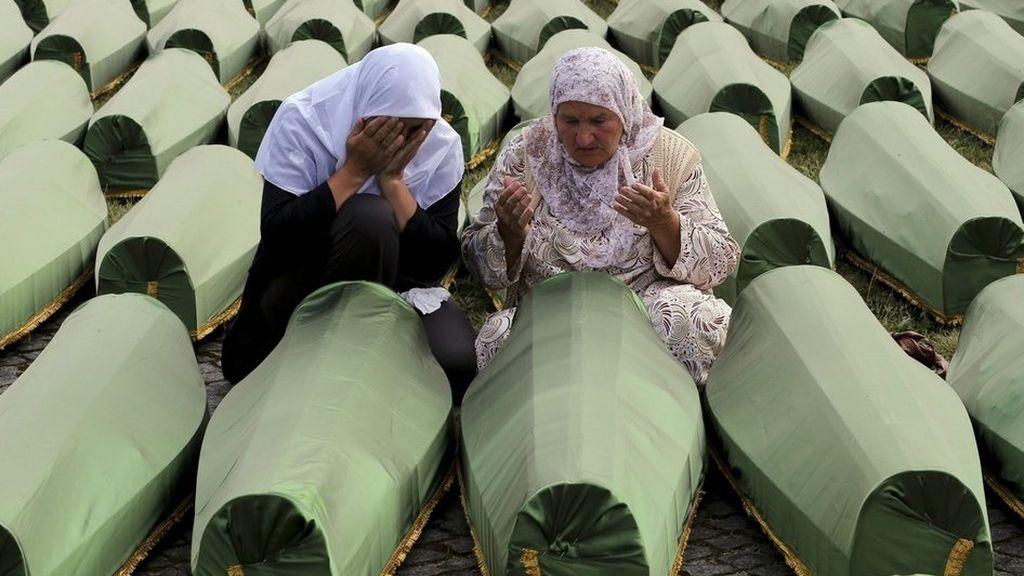 Mujeres rezan junto a féretros de sus familiares en Bosnia