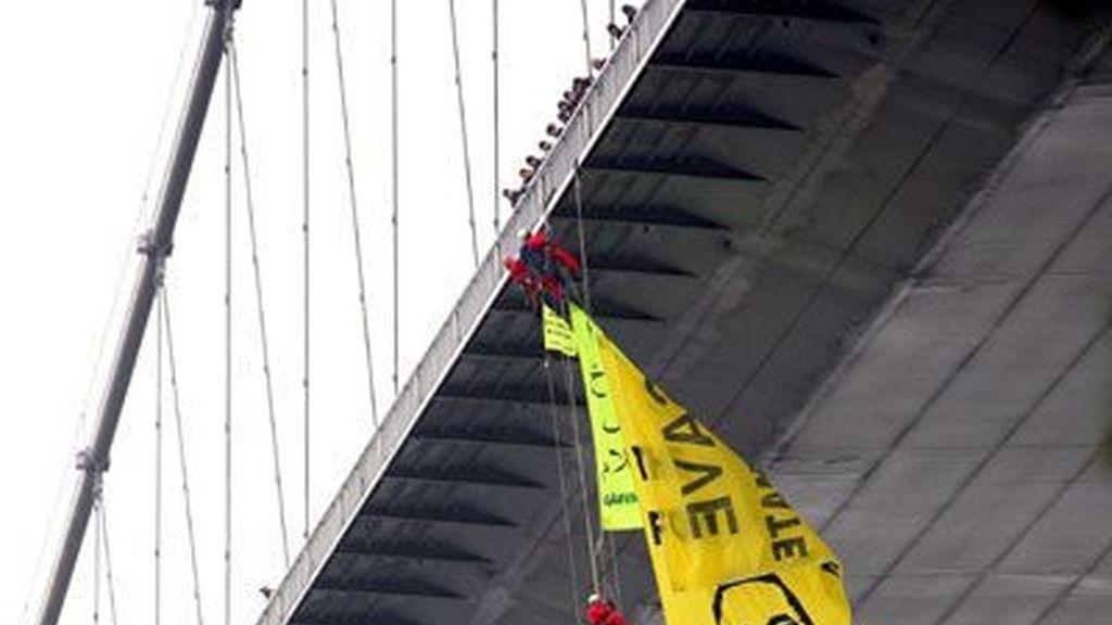 Activistas de Greenpeace cuelgan una pancarta  con el retrato de Obama