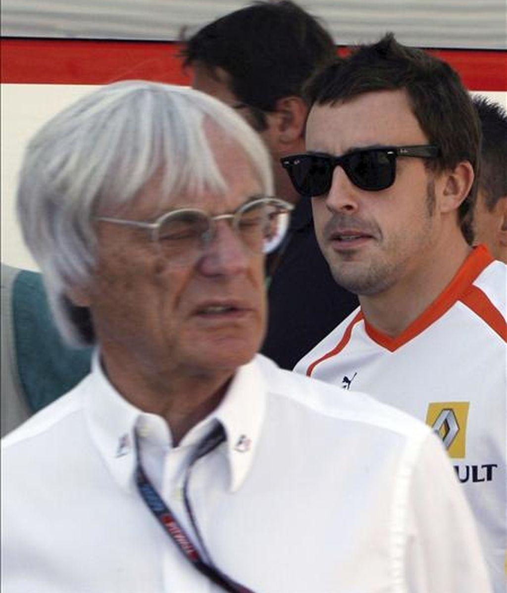 El piloto español Fernando Alonso (d) pasa junto al magnate británico de la F-1 Bernie Eclestone en el circuito ubano de Valencia el 23 de agosto pasado en el Gran Premio de Europa de Fórmula Uno. EFE/Archivo