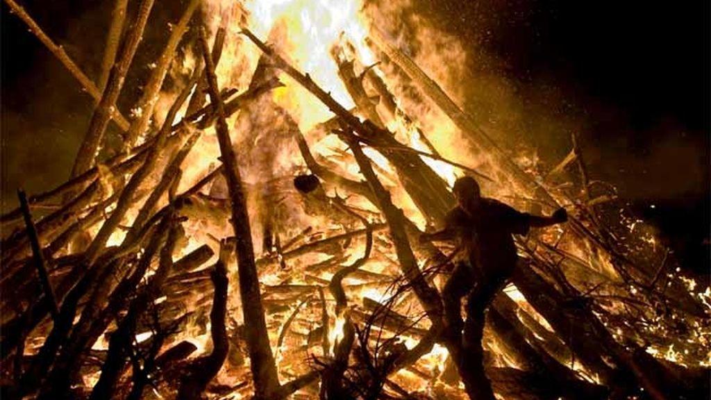 Un hombre salta entre las llamas durante la noche de San Juan en Burgos