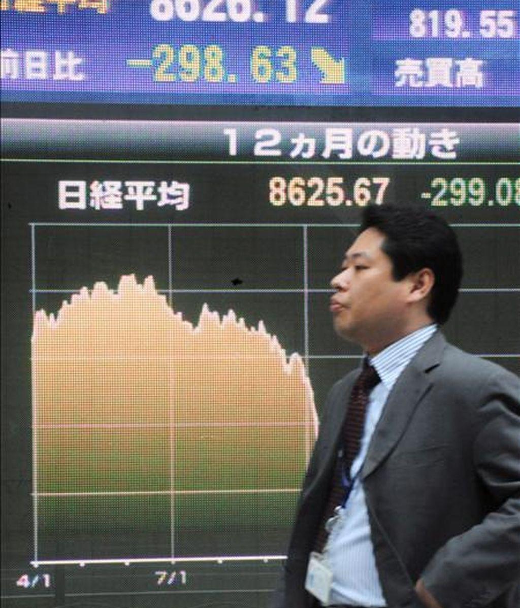 Un empresario japonés camina frente a un tablero con el índice Nikkei en el centro de Tokio. EFE/Archivo