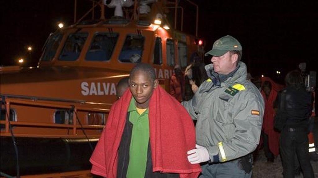 """Uno de los 33 inmigrantes subsaharianos, rescatados ayer en la Isla de Alborán, que han llegado esta madrugada en buen estado, a bordo de la embarcación """"Salvamar Hamal"""" de Salvamento marítimo, al Puerto de Motril (Granada) es ayudado por un guardia civil. EFE"""