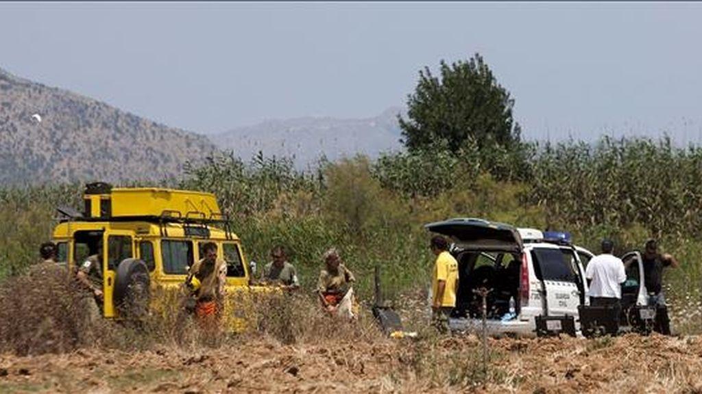 Agentes de la policía judicial de la Guardia Civil buscan pruebas en los alrededores del coche calcinado en cuyo maletero ha aparecido el cadáver de una mujer, en la carretera de Muro a Can Picafort (Mallorca). EFE