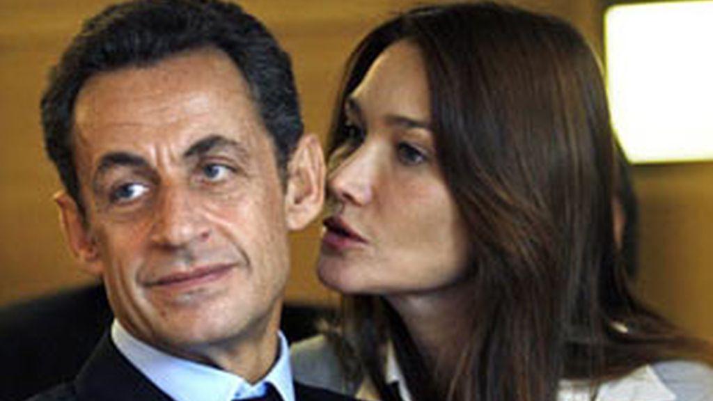 Carla Bruni le susurra algo al oido del presidente francés
