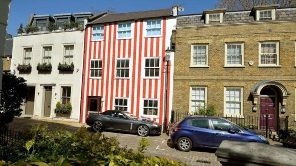 Una millonaria pinta la fachada de su casa con rayas rojiblancas para fastidiar a sus vecinos