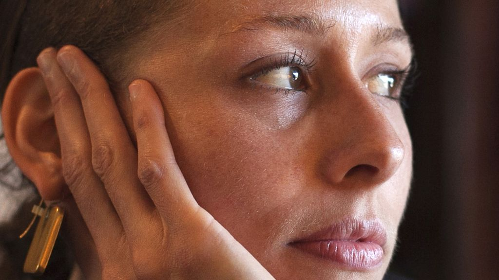 Una mujer mira preocupada a través de una ventana