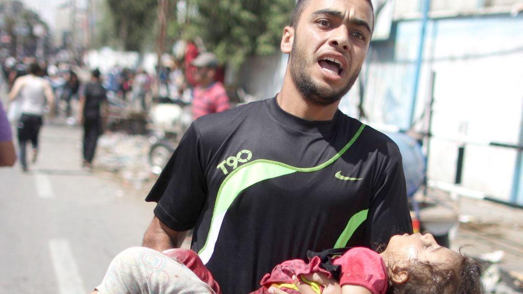 Un hombre palestino con el cadáver de una niña tras el ataque aéreo israelí