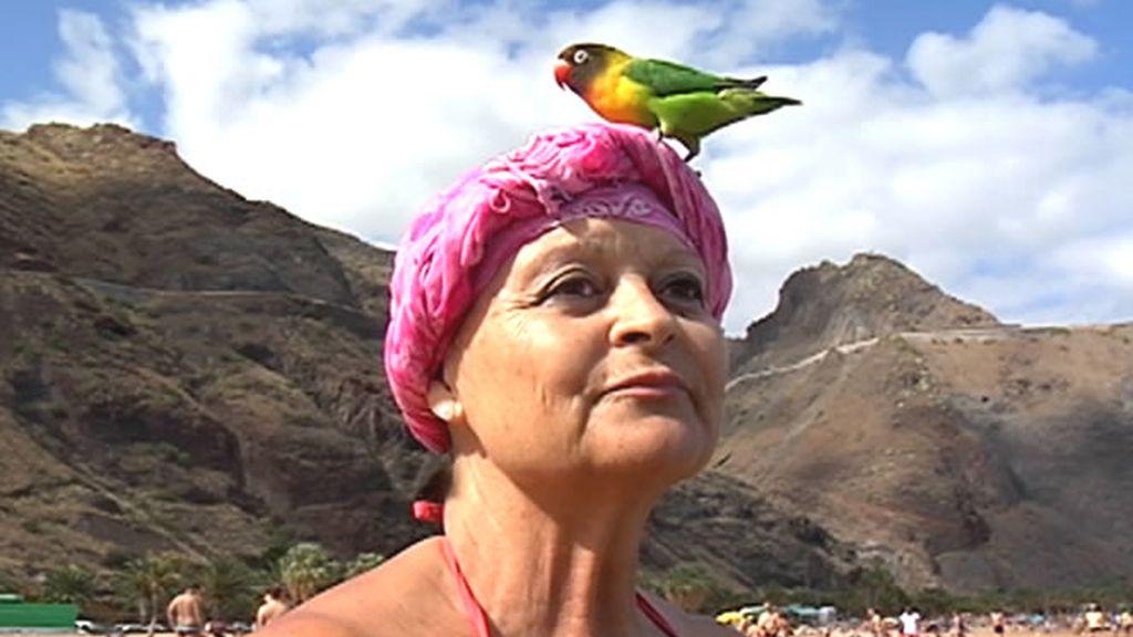 Una mujer sostiene un colorido pájaro en la cabeza